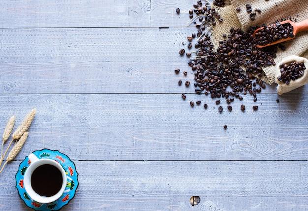 Grãos de café e café com outros componentes em fundo de madeira diferente. espaço livre para texto