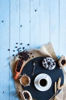 Grãos de café e café com outros componentes em fundo de madeira diferente.