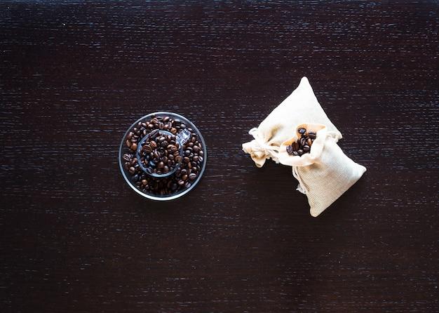Grãos de café e café com outros componentes na mesa de madeira diferente