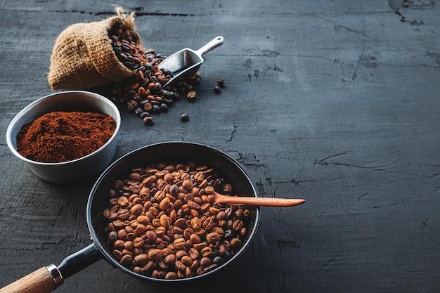 Grãos de café e café em pó em um fundo preto de madeira