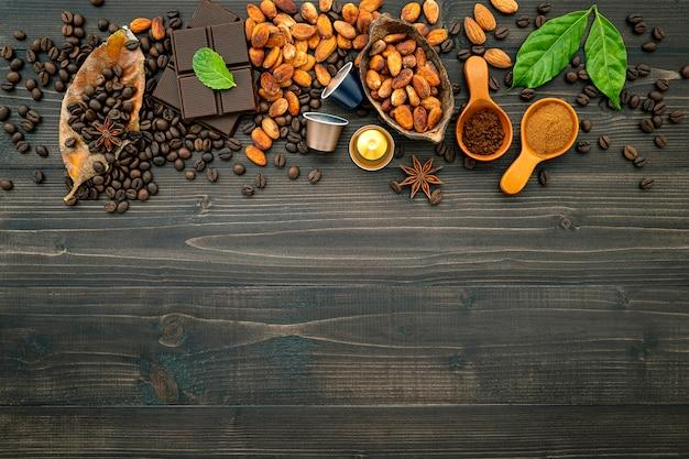 Grãos de café e café em pó na mesa de madeira escura.