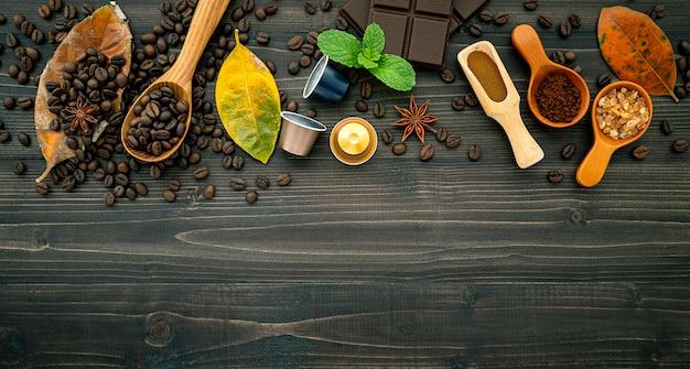 Grãos de café e café em pó no fundo escuro de madeira