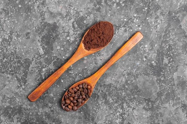 Grãos de café e café moído em colheres de madeira ecológicas em fundo cinza