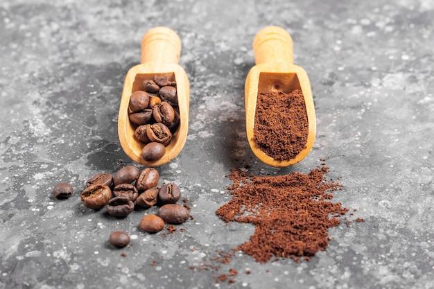 Grãos de café e café moído em pás de madeira em fundo cinza
