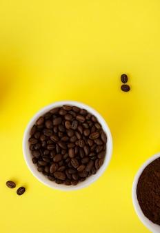Grãos de café e café moído em tigelas brancas sobre uma superfície amarela.