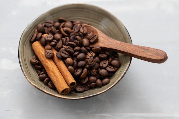 Grãos de café e canela com colher de pau em uma tigela pequena
