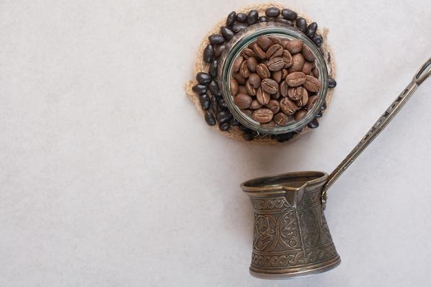 Grãos de café e cezve na superfície branca