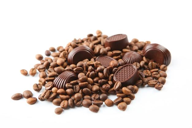 Grãos de café e chocolate na superfície branca isolados de perto