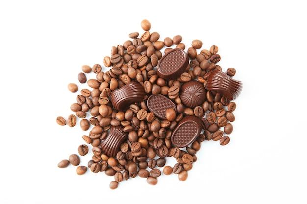 Grãos de café e chocolate no fundo branco isolados de perto