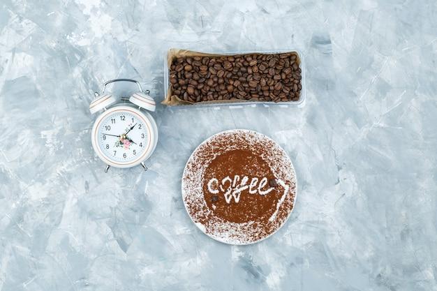 Grãos de café e despertador em fundo cinza sujo