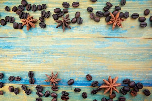 Grãos de café e estrelas de anis em fundo de madeira pintado em azul e dourado. lugar para texto.