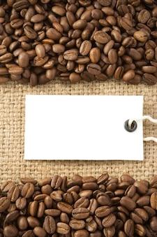Grãos de café e etiqueta de preço de papel na textura de saco de estopa