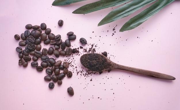 Grãos de café e grãos de café no fundo rosa