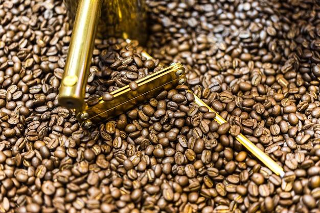 Grãos de café e grãos de café torrado assar na máquina de grãos de café torrador