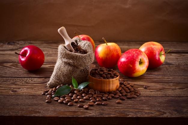Grãos de café e maçãs na textura de madeira