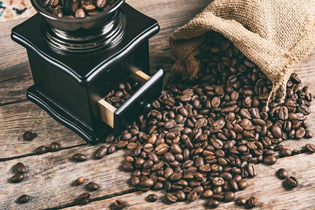 Grãos de café e moedor de café retro manual na mesa de madeira