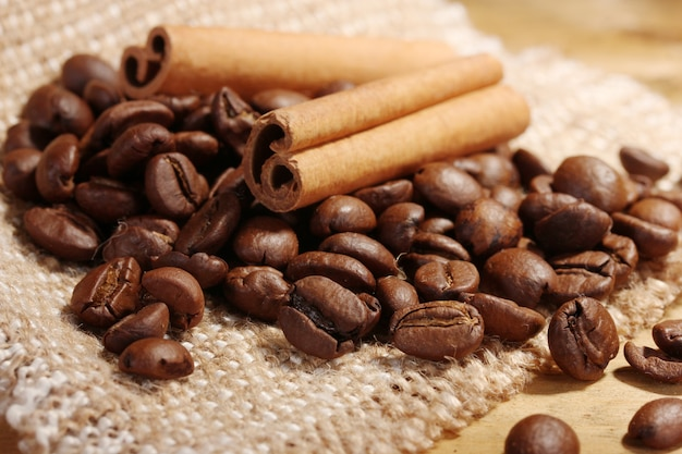 Grãos de café e paus de canela na sacaria na mesa de madeira