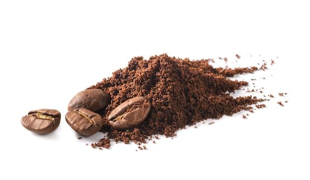 Grãos de café e pilha de café moído em um fundo branco. macro com departamento completo de campo