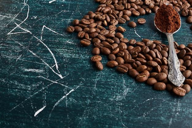Grãos de café e pó em uma colher metálica.