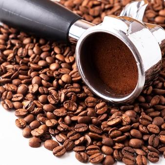 Grãos de café e porta-filtro para máquina de café.