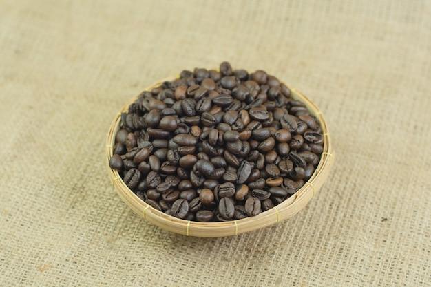 Grãos de café e tigela de madeira no fundo do saco de juta