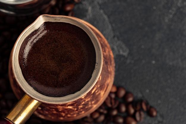 Grãos de café e turco na superfície escura