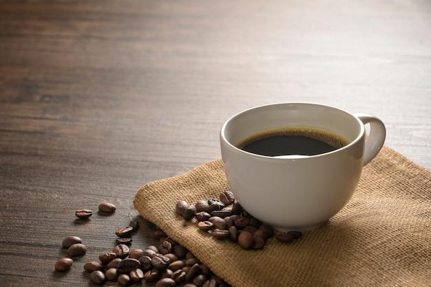 Grãos de café e uma xícara branca de café na bolsa saco em madeira fundo