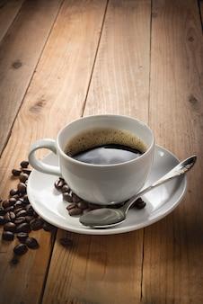 Grãos de café e uma xícara branca de café sobre fundo de madeira