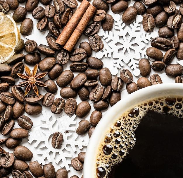 Grãos de café e xícara de café com especiarias aromáticas e decorações de natal. postura plana, diretamente acima
