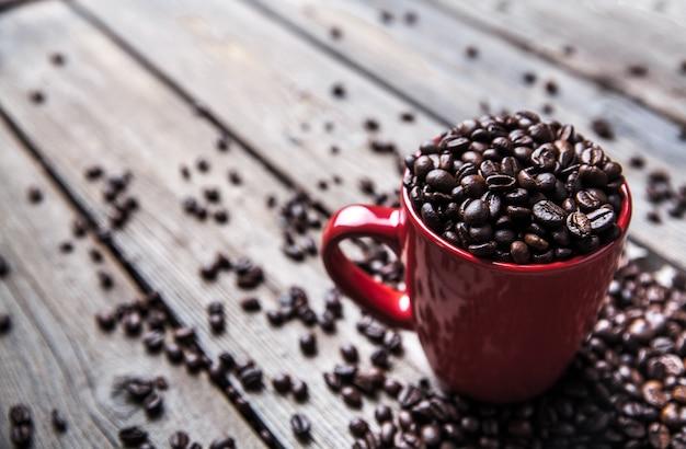 Grãos de café e xícara de café vermelha em fundo de madeira. beber