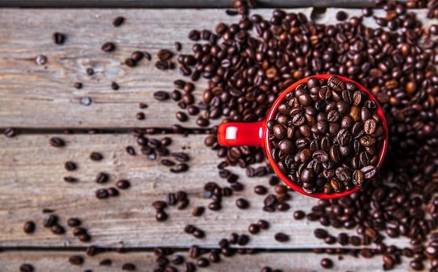Grãos de café e xícara de café vermelha em fundo de madeira.