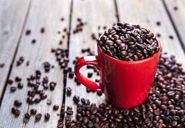 Grãos de café e xícara de café vermelha na madeira.
