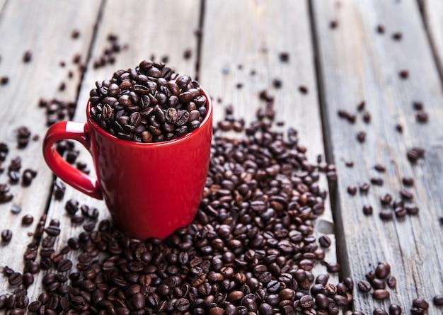 Grãos de café e xícara de café vermelha na mesa de madeira.