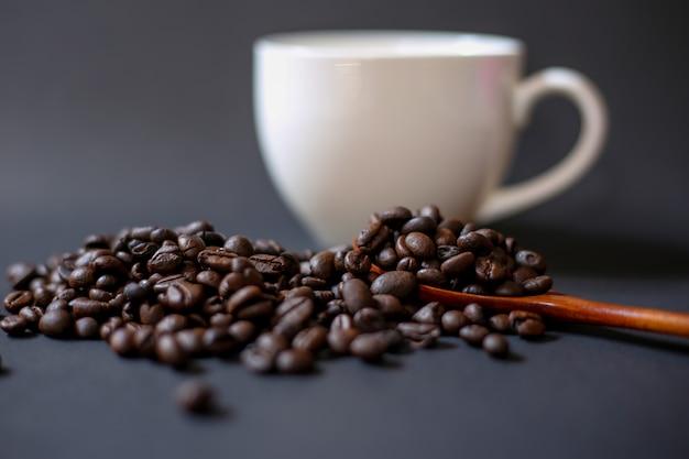 Grãos de café e xícaras brancas sobre um fundo escuro