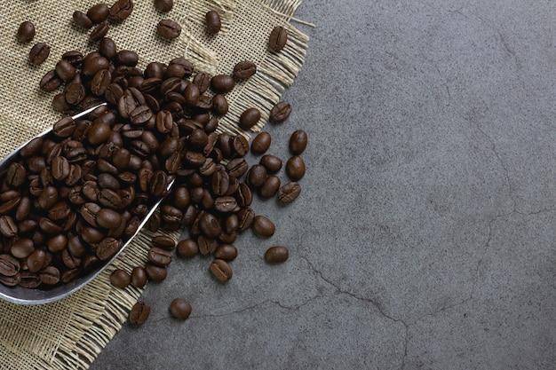 Grãos de café em colher na mesa