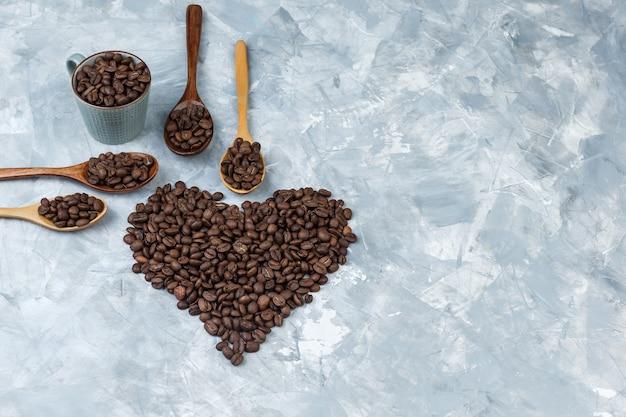 Grãos de café em colheres de madeira e xícara plana sobre um fundo de gesso cinza