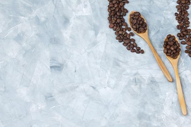 Grãos de café em colheres de madeira em um fundo de gesso cinza. colocação plana.