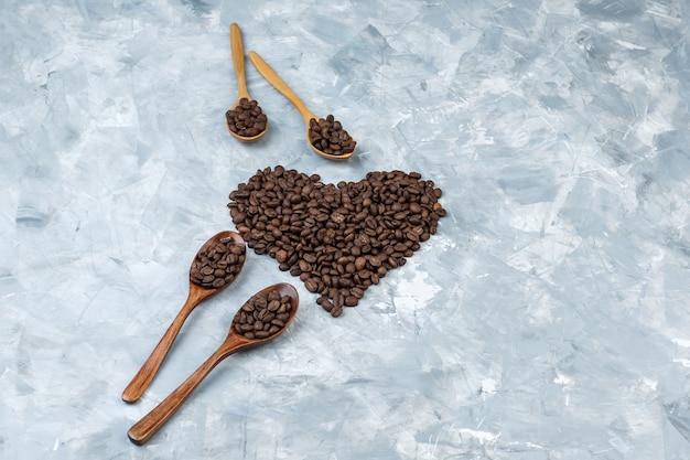 Grãos de café em colheres de madeira em um fundo de gesso cinza. vista de alto ângulo.