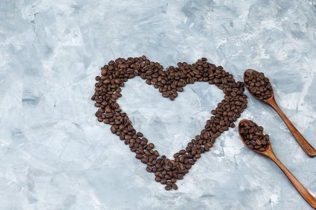 Grãos de café em colheres de madeira sobre um fundo de gesso cinza.