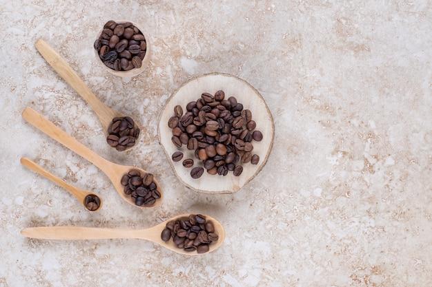 Grãos de café em colheres, um pedaço de madeira e uma xícara pequena