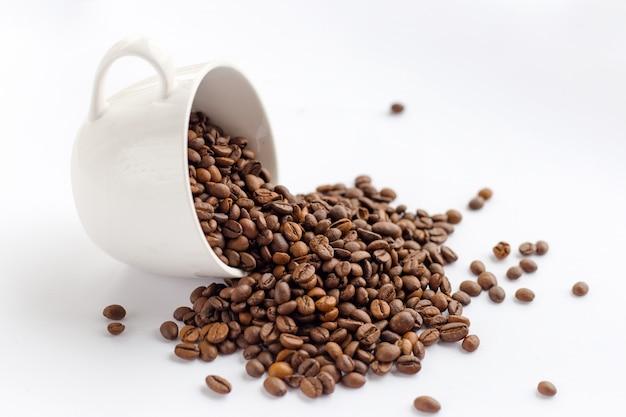 Grãos de café em copo branco isolado