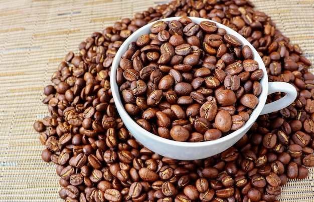 Grãos de café em copo branco no chão de madeira
