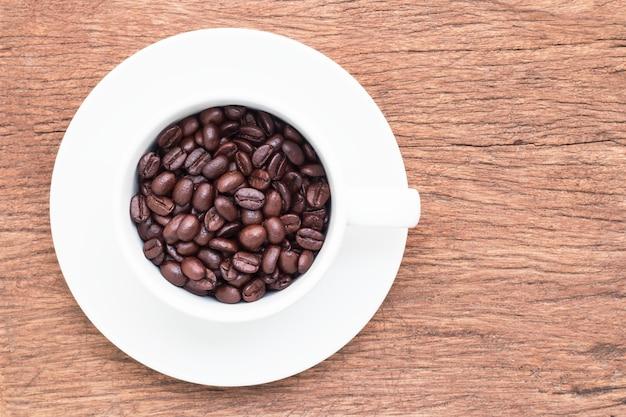 Grãos de café em copo branco no velho piso de prancha marrom com vista superior