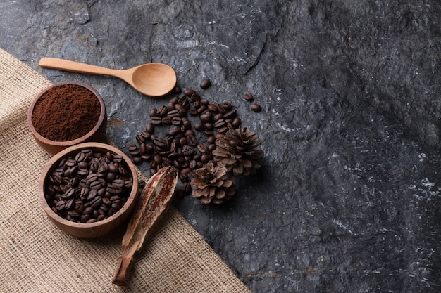 Grãos de café em copo de madeira na serapilheira, colher de madeira em fundo preto de pedra
