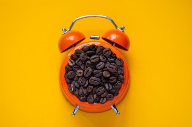 Grãos de café em despertador laranja