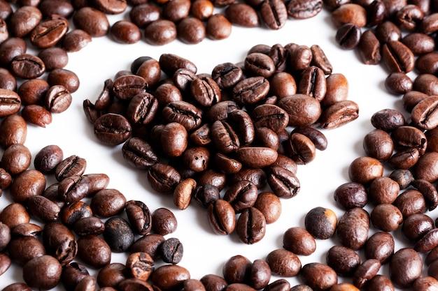 Grãos de café em forma de coração com fundo branco