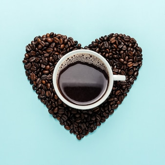 Grãos de café em forma de coração com xícara branca sobre azul.