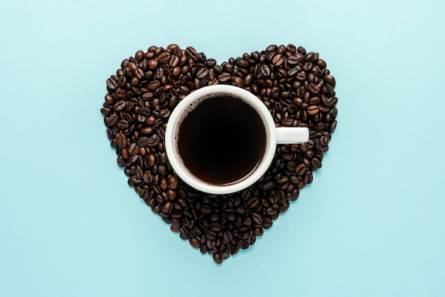 Grãos de café em forma de coração com xícara branca sobre fundo azul