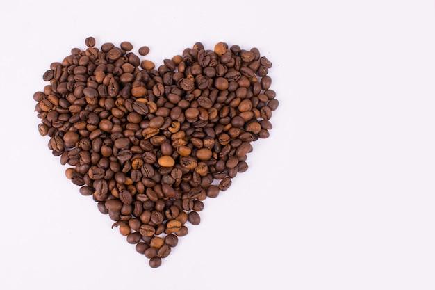 Grãos de café em forma de coração em fundo branco isolado