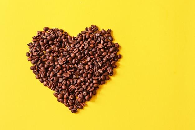 Grãos de café em forma de coração fundo branco isolado fundo amarelo
